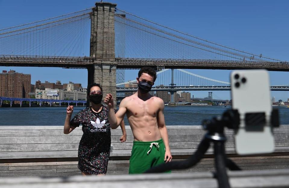 """<div class=""""inline-image__caption""""> <p>Actor Marie Zaccagnino and musican Sean Sheridan dance and record themselves with a mobile phone for a TikTok video in front of the Brooklyn Bridge on May 26, 2020, in New York City.</p> </div> <div class=""""inline-image__credit""""> Angela Weiss/AFP/Getty </div>"""