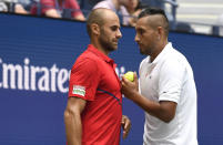 Nick Kyrgios, of Australia, right, talks with doubles partner Marius Copil, of Romania, during a first round match against Ken Skupski, of the United Kingdom, and Marcus Daniell, of New Zealand, during the US Open tennis championships Friday, Aug. 30, 2019, in New York. (AP Photo/Sarah Stier)