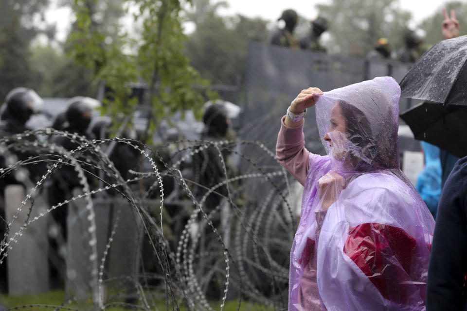 A woman stands at a barbed wire fence in front of a police line toward the Independence Palace, residence of the President Alexander Lukashenko, during Belarusian opposition supporters rally in Minsk, Belarus, Sunday, Sept. 6, 2020. Sunday's demonstration marked the beginning of the fifth week of daily protests calling for Belarusian President Alexander Lukashenko's resignation in the wake of allegedly manipulated elections. (AP Photo/TUT.by)