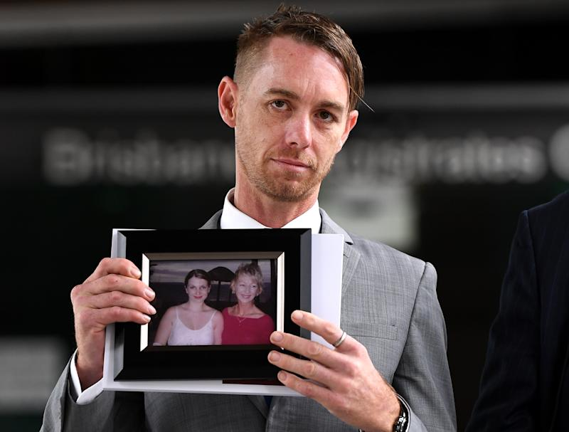 Michael Cooke, brother of Cindy Low, holds a picture of her in front of Brisbane's Magistrates Court. Source: AAP