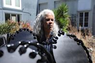 """Sculptor Dana King stands among """"ancestor"""" statues she created for an upcoming exhibit called """"Monumental Reckoning"""" while at her studio in Oakland"""