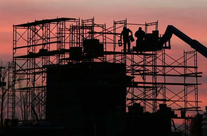 Construction crew erects scaffolding at sunset on a new housing project in Maryland