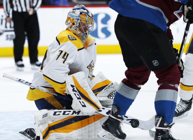 Nashville Predators goaltender Juuse Saros, left, makes a stick save of a redirected shot off the stick of Colorado Avalanche center Carl Soderberg during the first period of an NHL hockey game Friday, March 16, 2018, in Denver. (AP Photo/David Zalubowski)