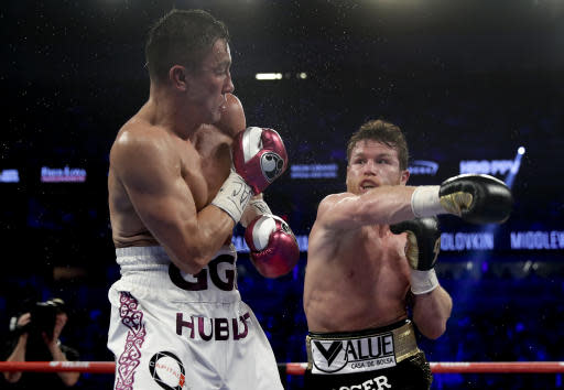Gennady Golovkin, left, and Canelo Alvarez trade punches in the fifth round during a middleweight title boxing match, Saturday, Sept. 15, 2018, in Las Vegas. (AP Photo/Isaac Brekken)