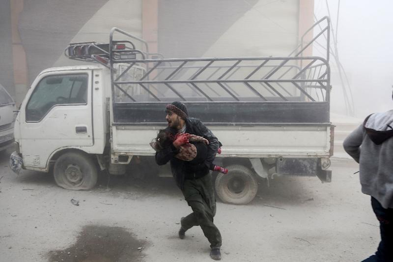 A man carries a child as he flees from reported Syrian air strikes in rebel-held Eastern Ghouta on February 6, 2018 (AFP Photo/ABDULMONAM EASSA)