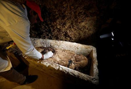 A Egyptian archaeologist examines a mummy in a coffin inside a tomb during the presentation of a new discovery at Tuna el-Gebel archaeological site in Minya Governorate, Egypt, February 2, 2019. REUTERS/Amr Abdallah Dalsh