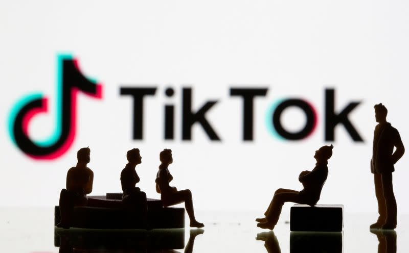 FILE PHOTO: Small toy figures are seen in front of a Tiktok logo in this illustration taken