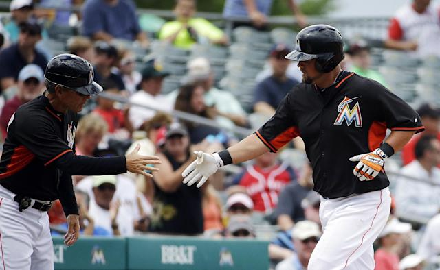 Miami Marlins' Casey McGehee, right, shakes hands with third base coach Brett Butler after hitting a home run in the fourth inning of an exhibition spring training baseball game against the St. Louis Cardinals, Tuesday, March 25, 2014, in Jupiter, Fla. (AP Photo/David Goldman)
