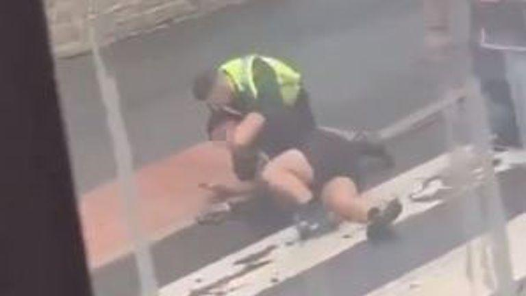 An officer grapples with the man and appears to say 'chill out or I'll choke you out'