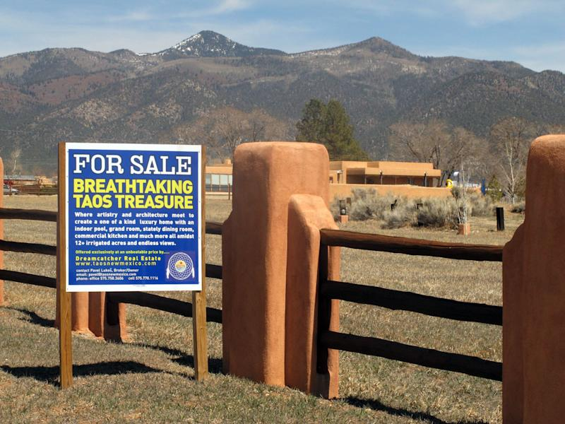 In this March 26, 2013 photo, a for sale sign on a property on the Arroyo Hondo Land Grant, the historical northern New Mexico Spanish land grant. Heirs and homeowners currently are locked in a dispute after a land grant board filed a warranty deed in an attempt to reclaim 20,000 acres of private land originally granted by Spain's colonial government to Arroyo Hondo's founding families. The fight is preventing homeowners from selling property, refinancing mortgages, or getting insurance policies while the courts struggle to unravel the conflict. (AP Photo/Russell Contreras)