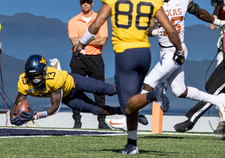 West Virginia wide receiver Sam James (13) catches a touch pass during the first half of an NCAA college football game Saturday against Texas, Oct. 5, 2019, in Morgantown, W.Va. (AP Photo/Raymond Thompson)