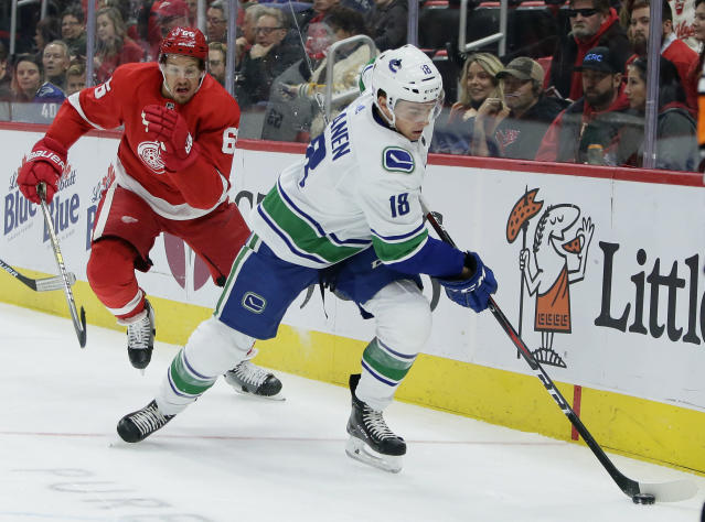 Detroit Red Wings defenseman Danny DeKeyser (65) pursues Vancouver Canucks right wing Jake Virtanen (18) behind the net during the first period of an NHL hockey game Tuesday, Nov. 6, 2018, in Detroit. (AP Photo/Duane Burleson)