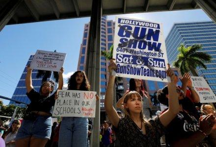 A protester holds a defaced placard at a rally calling for more gun control three days after the shooting at Marjory Stoneman Douglas High School, in Fort Lauderdale, Florida, U.S.,February 17, 2018. REUTERS/Jonathan Drake
