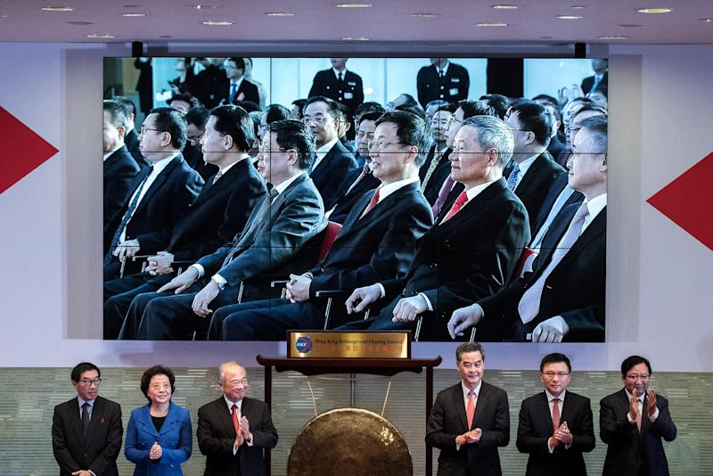 Local officials take part in the launch of the Shanghai-Hong Kong Stock Connect, in Hong Kong, on November 17, 2014, as a live broadcast shows a ceremony taking place in Shanghai (AFP Photo/Philippe Lopez)