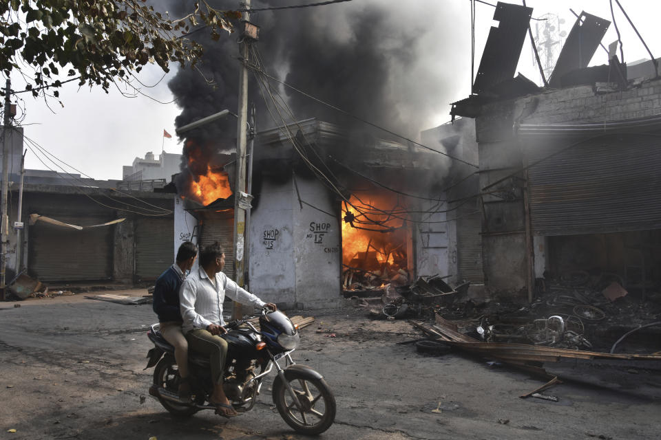 A motorcyclist drives past shops that were set on fire by mobs in New Delhi, India, Wednesday, Feb. 26, 2020. At least 20 people were killed in three days of clashes in New Delhi, with the death toll expected to rise as hospitals were overflowed with dozens of injured people, authorities said Wednesday. The clashes between Hindu mobs and Muslims protesting a contentious new citizenship law that fast-tracks naturalization for foreign-born religious minorities of all major faiths in South Asia except Islam escalated Tuesday. (AP Photo/Dinesh Joshi)