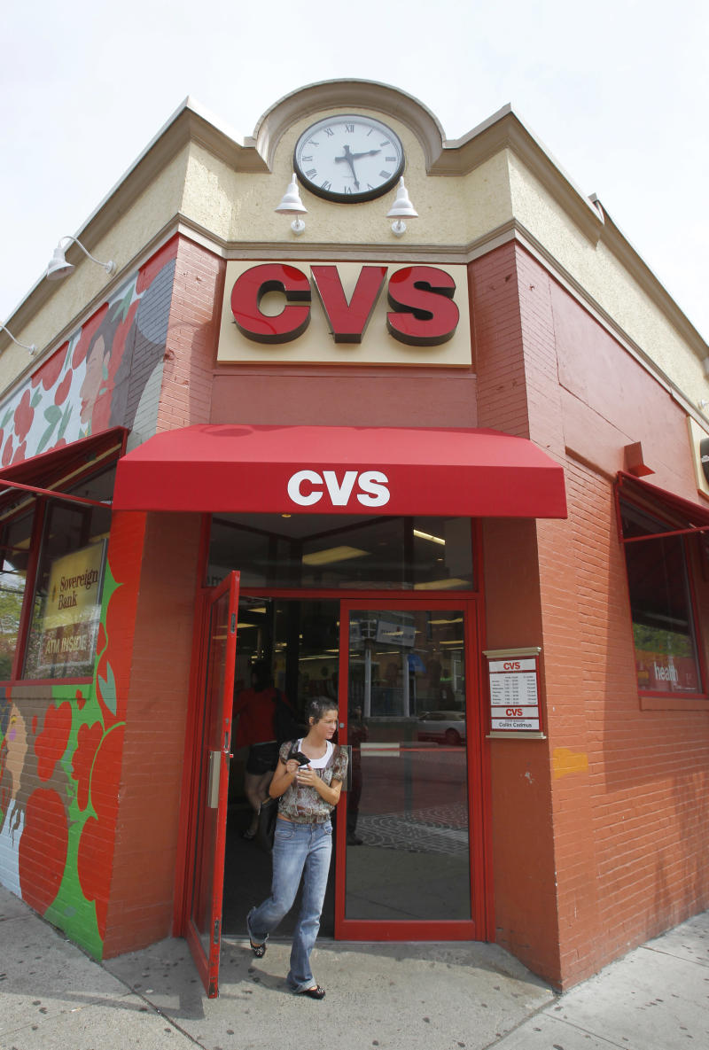 FILE - A May 3, 2011 file photo,shows a customer exiting a CVS store in Providence, R.I.  CVS Caremark said Monday May2, 2012,  its first-quarter earnings rose 9 percent, as the drugstore operator and pharmacy benefits manager gained customers from an acquisition and a competitor's contract dispute.  (AP Photo/Steven Senne, file)