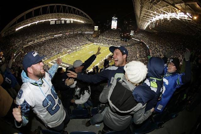 Seattle Seahawks fans celebrate after Seahawks' Michael Bennett recovered a New Orleans Saints fumble and scored a touchdown in the first half of an NFL football game, Monday, Dec. 2, 2013, in Seattle. (AP Photo/John Froschauer)