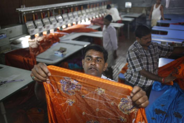 In this Monday, Sept. 2, 2013 photo, Indian Pradeep Kumar Yadav, 42, inspects a finished product at his embroidery factory in Varanasi, India. Pradeep, owner of a fast-expanding manufacturer of water pumps and electric fans, says he finds stocks confusing and prefers investing in real estate and putting money back into his business. (AP Photo/ Rajesh Kumar Singh)