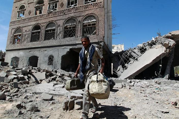 A Yemeni man carries his bags through the ruins of buildings destroyed in an air strike by the Saudi-led coalition in the capital Sanaa on October 28, 2015 (AFP Photo/Mohammed Huwais)