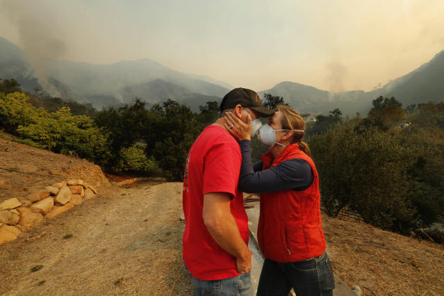 <p>Dan Bellaart and his wife Mary McEwen comfort each other in the back yard of their home that includes an avocado ranch on 9 acres of land on Toro Canyon Rd. as the Thomas fire burns in the background on Dec., 11, 2017 in Montecito, Calif. They have lived here since 2002. (Photo: Mel Melcon/Los Angeles Times via Getty Images) </p>