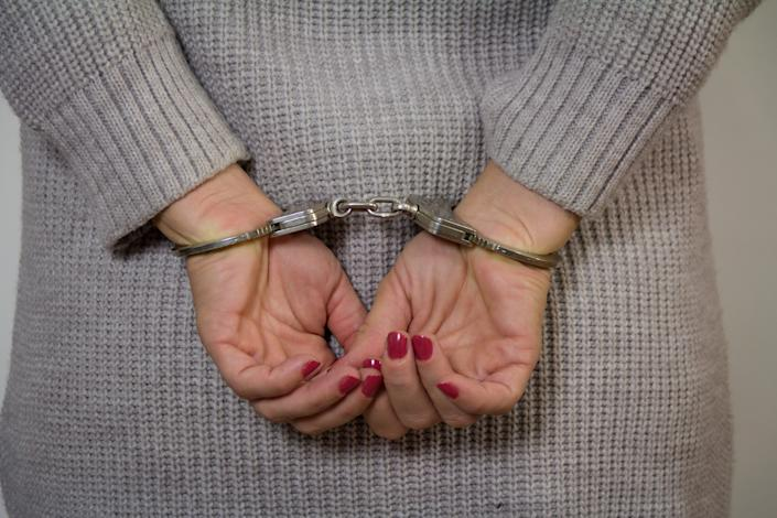 Woman in handcuffs. (PHOTO: Getty Images)