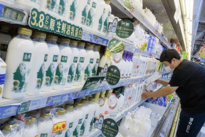 Staff member places cartons of milk on refrigerator shelves at a supermarket in Beijing