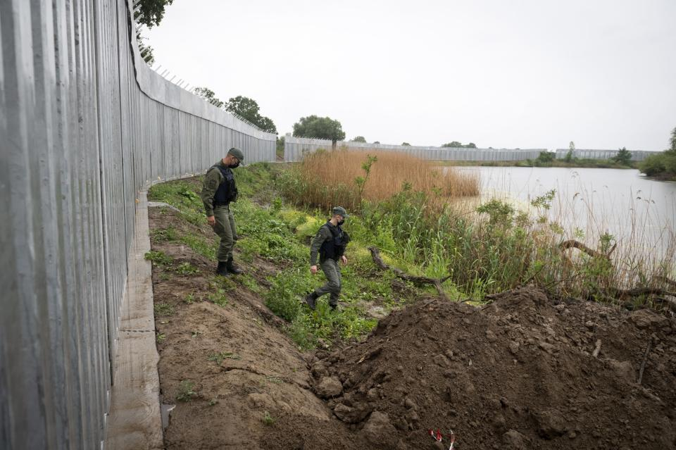FILE - In this May 21, 2021, file photo, policemen patrol alongside a steel wall at Evros river, near the village of Poros, at the Greek -Turkish border, Greece. Haunted by a 2015 migration crisis fueled by the Syrian war, European leaders desperately want to avoid another large-scale influx of migrants and refugees from Afghanistan. (AP Photo/Giannis Papanikos, File)