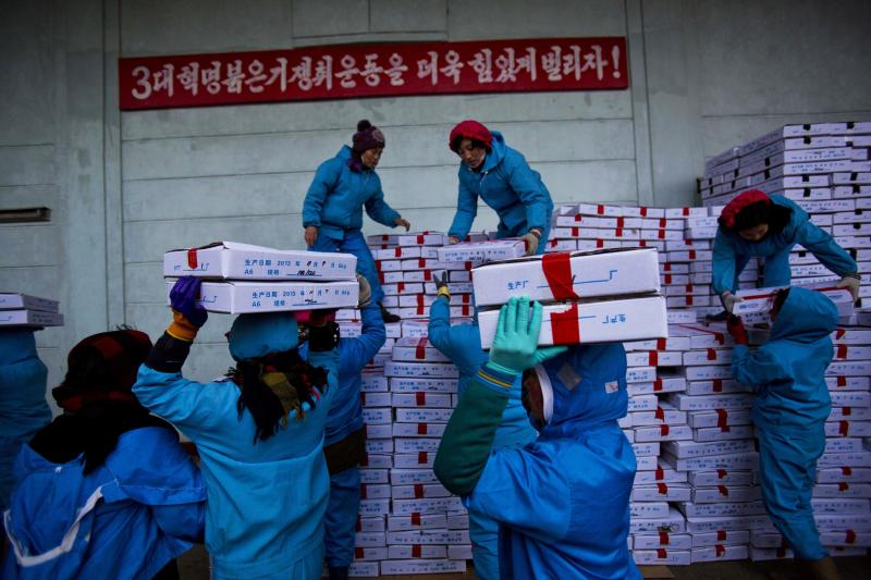 "In this Friday, Nov. 8, 2013 photo, North Korean workers carry boxes of seafood as they load a Chinese transport truck at the Suchae Bong Corp seafood factory in Rajin, North Korea inside the Rason Special Economic Zone. Last month, North Korea announced plans to create economic zones in every province. The North also recently laid out new laws to facilitate foreign tourism and investment. The laws provide investors with special incentives and guarantees, while giving local leaders greater autonomy to promote themselves and handle business decisions. The sign on the wall in Korean reads, ""Let's work harder on the third generation revolution movement to win the red flag!"" (AP Photo/David Guttenfelder)"