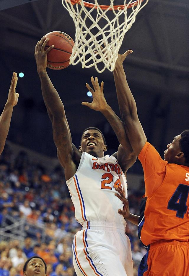 Florida forward Casey Prather (24) goes to the basket as Savannah State's Jyles Smith defends during the first half of an NCAA college basketball in Gainesville, Fla., Sunday, Dec. 29, 2013. (AP Photo/Phil Sandlin)