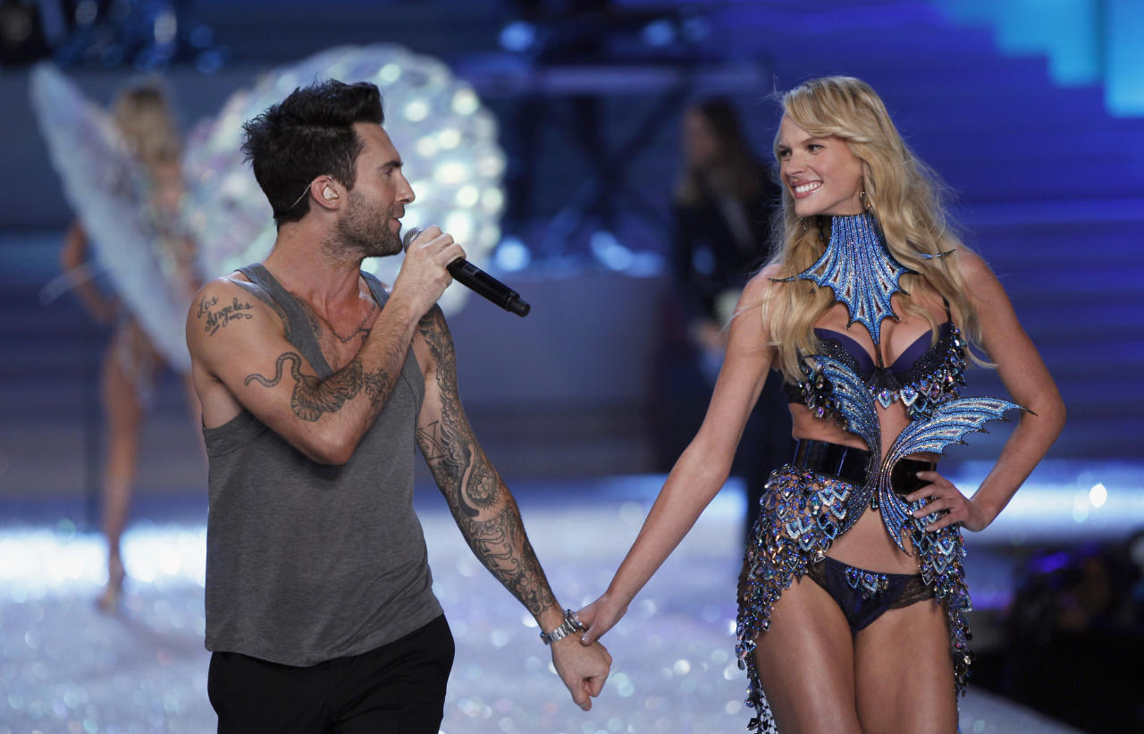 Adam Levine (L), lead singer of the group Maroon 5, walks down the runway with model Anne Vyalitsyna as she presents a creation during the Victoria's Secret Fashion Show at the Lexington Armory in New York November 9, 2011. REUTERS/Lucas Jackson (UNITED STATES - Tags: ENTERTAINMENT FASHION)