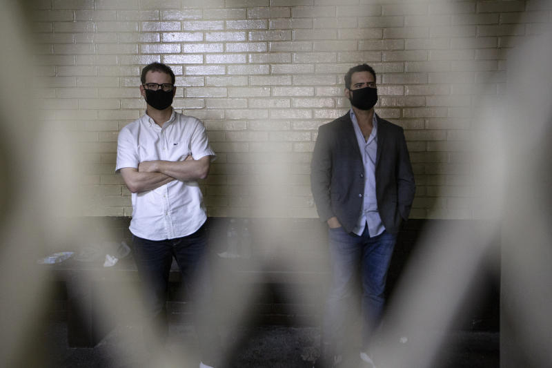 The sons of former Panamanian President Ricardo Martinelli, Ricardo Martinelli Linares, right, and his brother Luis Enrique stand inside a holding cell at the judicial court building in Guatemala City, Tuesday, July 7, 2020. The brothers were detained Monday on an international warrant from Interpol on charges of conspiracy to commit money laundering. (AP Photo/Moises Castillo)