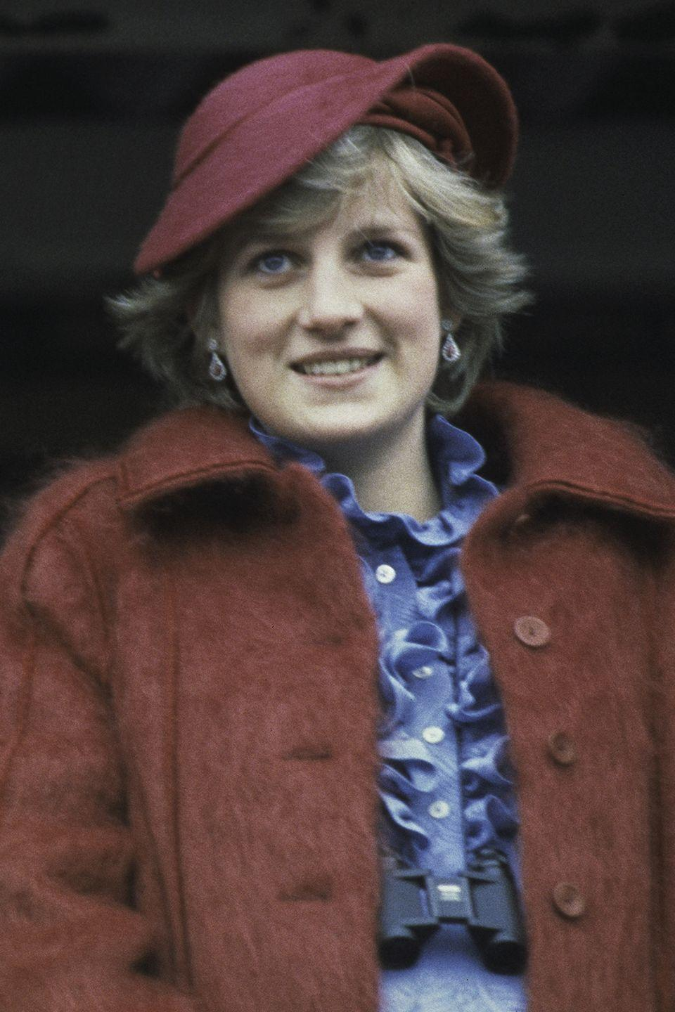 <p>Wearing a burgundy hat while attending the Aintree racecourse for the Grand National. </p>