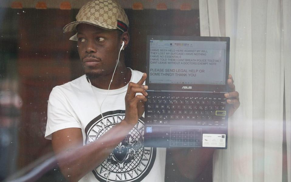 Anthony Pium held his laptop up to a window at the hotel, with a message typed on its screen appealing for legal help to be freed from quarantine -  Jonathan Brady/PA