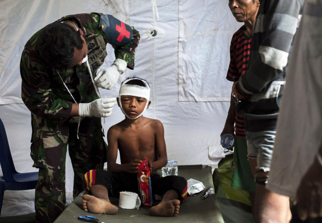 <p>A military paramedic tends to a boy who suffers head injury from Sunday's earthquake at a makeshift hospital in Kayangan, Lombok Island, Indonesia, Wednesday, Aug. 8, 2018. (Photo: Fauzy Chaniago/AP) </p>