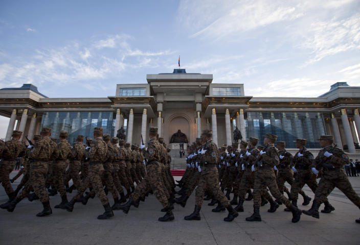 In this July 9, 2012 photo, Mongolian soldiers take part in a rehearsal for a military parade during the Naadam Festival in front of Parliament on the Sukhbaatar Square in Ulan Bator, Mongolia. Landlocked with 2.8 million people spread over an area twice the size of Texas, Mongolia is dwarfed by China, with its 1.3 billion people and the world's second largest economy. Fully 90 percent of Mongolia's exports - coal, copper, cashmere and livestock - go to China, which in turn sends machinery, appliances and other consumer goods that account for a third of Mongolian imports. (AP Photo/Andy Wong)