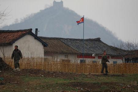 North Korean people walk in a field as a section of the Great Wall is seen on the Chinese side of the Yalu River, north of the town of Sinuiju in North Korea and Dandong in China