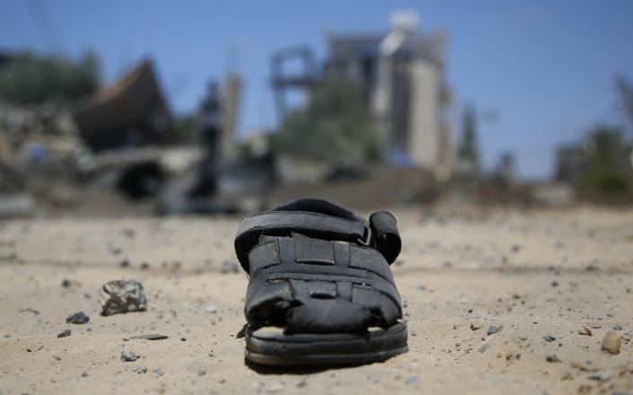 CORRECTS DATE TO MONDAY, MAY 17, 2021, NOT TUESDAY, DEC. 3, 2019 - A sandal lies on the ground after a house was hit by early morning Israeli airstrikes in Beit Lahyia, northern Gaza Strip, on Monday, May 17, 2021. The Israeli military unleashed a wave of heavy airstrikes Monday on the Gaza Strip, saying it destroyed 15 kilometers (9 miles) of militant tunnels and the homes of nine Hamas commanders as international diplomats worked to end the weeklong war that has killed hundreds of people. (AP Photo/Hatem Moussa)