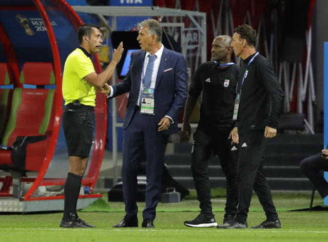 FILE - In this file photo from June 20, 2018, Iran head coach Carlos Queiroz, second left, talks to an assistant referee during the Group B match between Iran and Spain at the World Cup in Kazan, Russia, Spain won 1-0. (AP Photo/Sergei Grits, File)