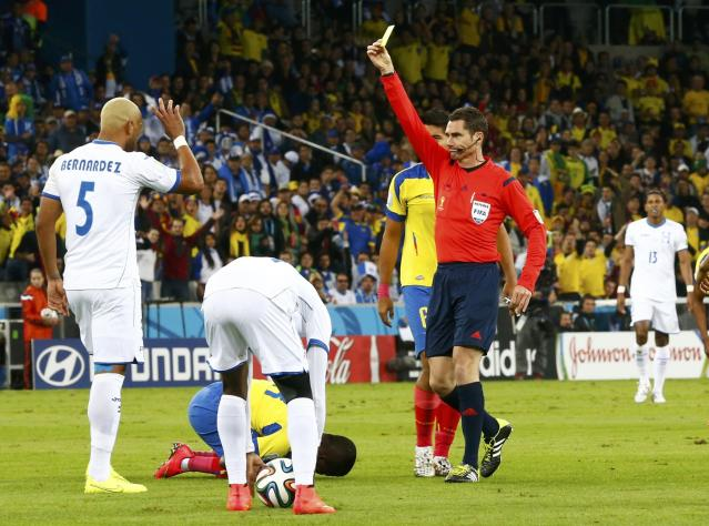 Victor Bernardez of Honduras (L) reacts after being shown the yellow card during their 2014 World Cup Group E soccer match against Ecuador at the Baixada arena in Curitiba June 20, 2014. REUTERS/Darren Staples (BRAZIL - Tags: SOCCER SPORT WORLD CUP)