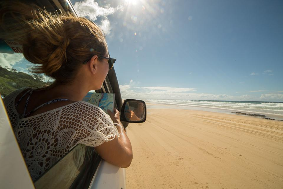 Young woman in a car reads a road map, Fraser Island.