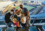 Voters Brandon Malmberg and wife, Debbie take a selfie with their sons, Ashton, 7, Penn, 6, and Emmett 4, after voting in-person on Election Day at Dodger Stadium in Los Angeles, Tuesday, Nov. 3, 2020. Far left, is family au pair, Marco Mosquera, originally from Colombia. (AP Photo/Damian Dovarganes)
