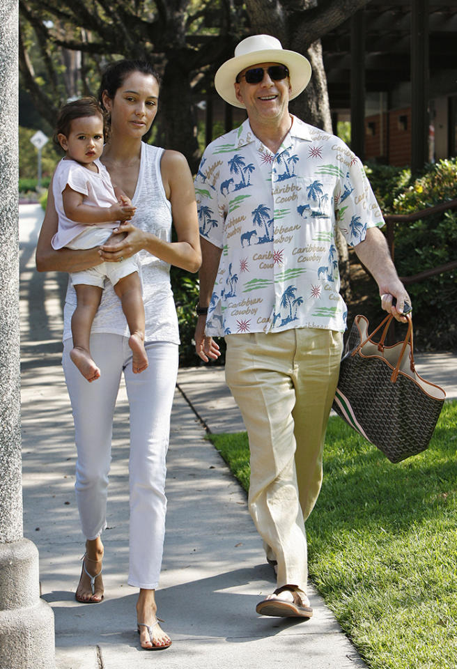 "Since wife Emma Hemming had his hands full with their 14-month-old daughter, Mabel, A-list actor happily carted her purse during the family's stroll to the park. And if you're having trouble reading Bruce's shirt, it says ""Caribbean Cowboy"" all over it. Interesting ... (6/30/2013)"