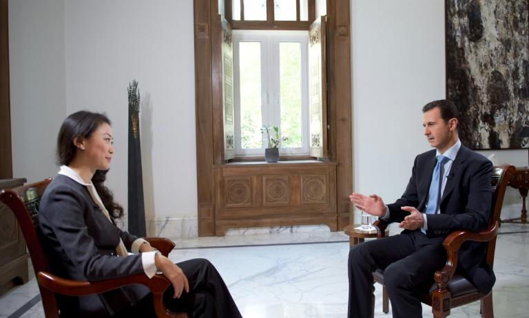 Bashar al-Assad (right) speaks with a journalist from China's Phoenix television on November 22, 2015, in Damascus