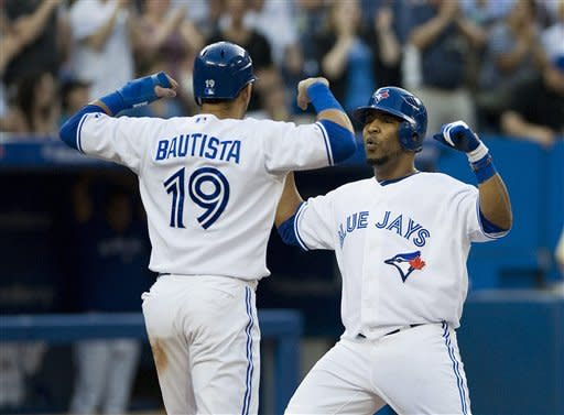 Toronto Blue Jays Edwin Encarnacion celebrates his homer with Jose Bautista who scored on the play during the third inning against the Baltimore Orioles during a baseball game in Toronto Monday May 28, 2012. (AP Photo/The Canadian Press, Aaron Vincent Elkaim)