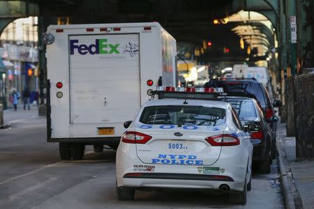 A NYPD patrol car sits parked behind an illegally parked FedEx truck in the Queens borough of New York January 7, 2015. REUTERS/Shannon Stapleton