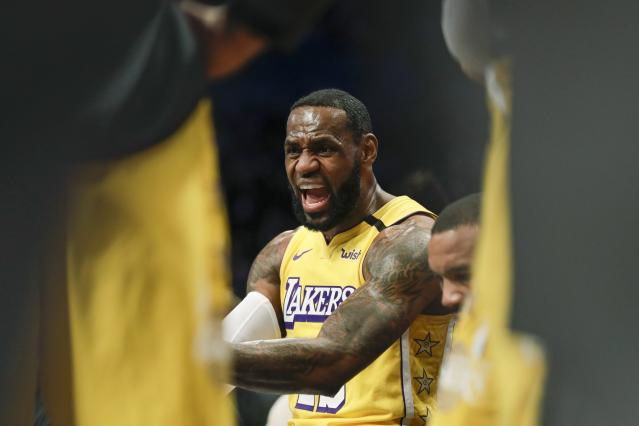 Los Angeles Lakers' LeBron James talks to teammates during a timeout in the first half of an NBA basketball game against the Brooklyn Nets Thursday, Jan. 23, 2020, in New York. (AP Photo/Frank Franklin II)