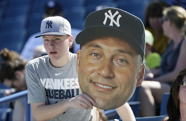 A fan holds a large photo of New York Yankees shortstop Derek Jeter during spring training baseball practice Thursday, Feb. 20, 2014, in Tampa, Fla. (AP Photo/Charlie Neibergall)