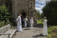 """The Rev. Jonathan Gordon, left, and Assistant Vicar Miranda Sheldon, right, greet Anglican worshippers who attended their first communal prayer service after pandemic restrictions were eased, at St. Mary's Church, Northchurch in Berkhamsted, England, on Sunday, July 5, 2020. On March 24, the Church of England closed all its buildings. """"It posed an immediate and immense challenge,"""" Gordon says. """"It meant that we had to completely rethink how we did everything."""" (AP Photo/Elizabeth Dalziel)"""