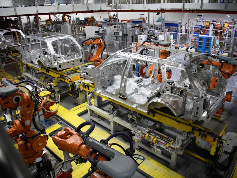 Robotic systems work on the chassis of a car during an automated stage of production at the Jaguar Land Rover factory: Getty