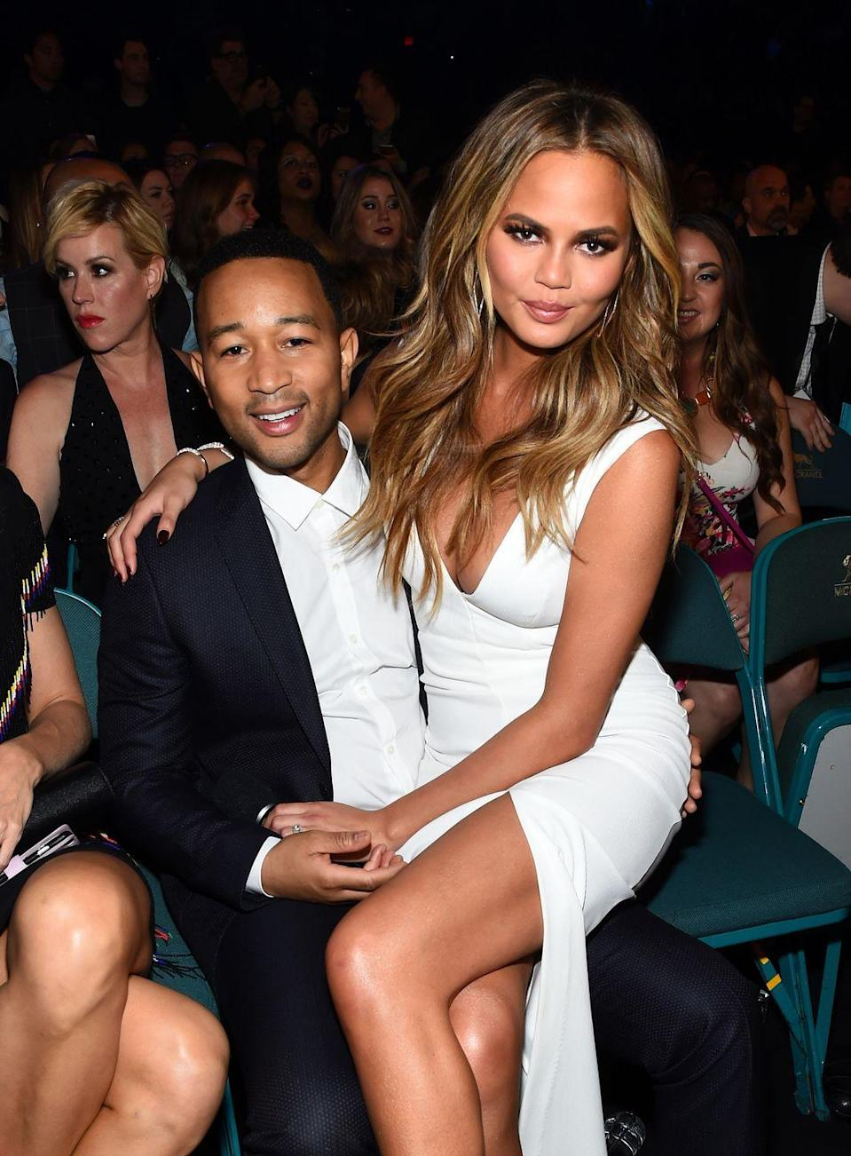 <p>Teigen takes a break from hosting the 2015 Billboard awards to perch on her husband's knee.</p>